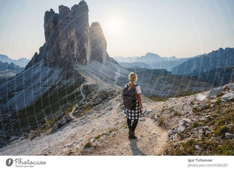 Women hiker with backpack enjoying the Tre Cime di Lavaredo during sunset. Dolomites, Italy lavaredo three peaks mountain landscape woman nature alpine travel
