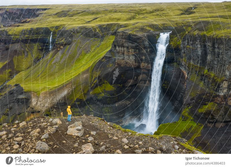 Aerial view of man standing on the cliff edge enjoying Iceland highland valley and Haifoss waterfall aerial landscape river above iceland haifoss stream green