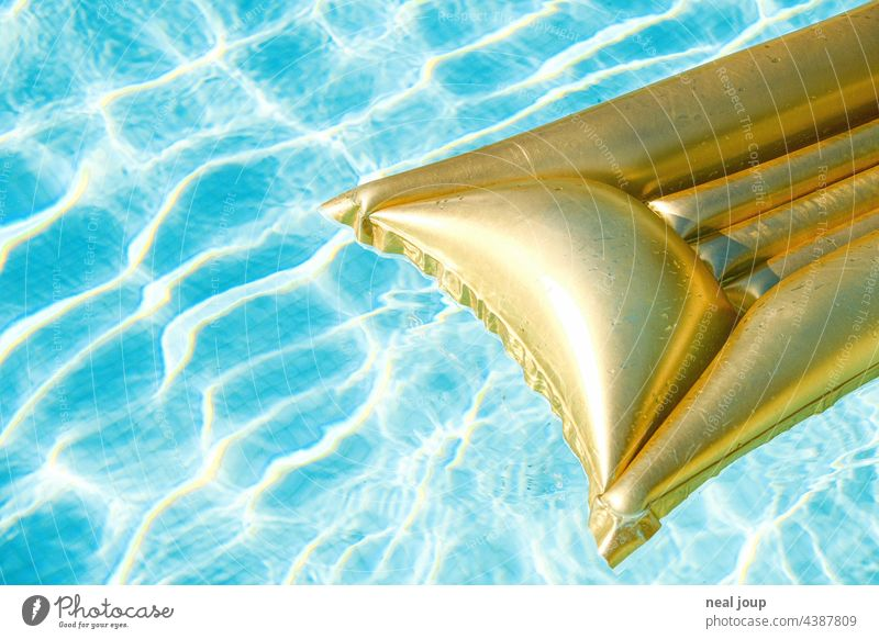 Golden air mattress in crystal clear water with light reflections vacation Break Summer vacation pool pool party Water Blue reflexes Relaxation