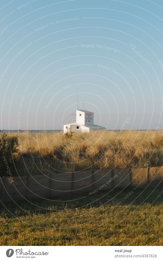 Cubist building of the Life Guards behind dune grass at the sea in front of blue sky. Ocean Horizon Building Container cubistic Architecture Blue sky White
