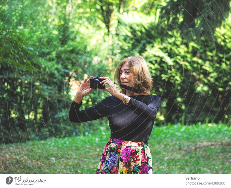senior active blond caucasian woman photographing in park outdoors in mid season beauty nature hair people forest smiling person dress face blonde fashion grass