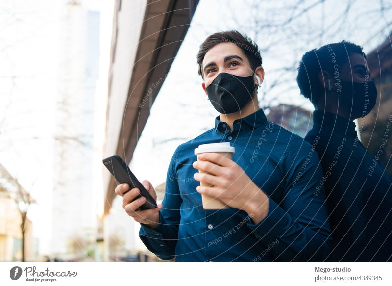 Young man using his mobile phone outdoors. young urban face mask covid-19 connection protection coffee portrait wireless telephone holding cup of coffee
