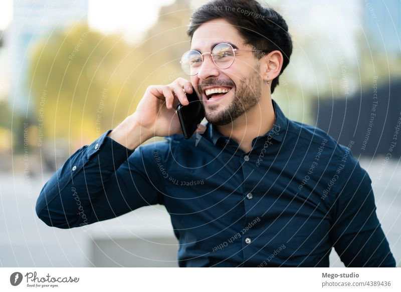 Young man talking on the phone outdoors. young mobile urban smiling smile connection gadget portrait positive wireless telephone holding walking looking typing