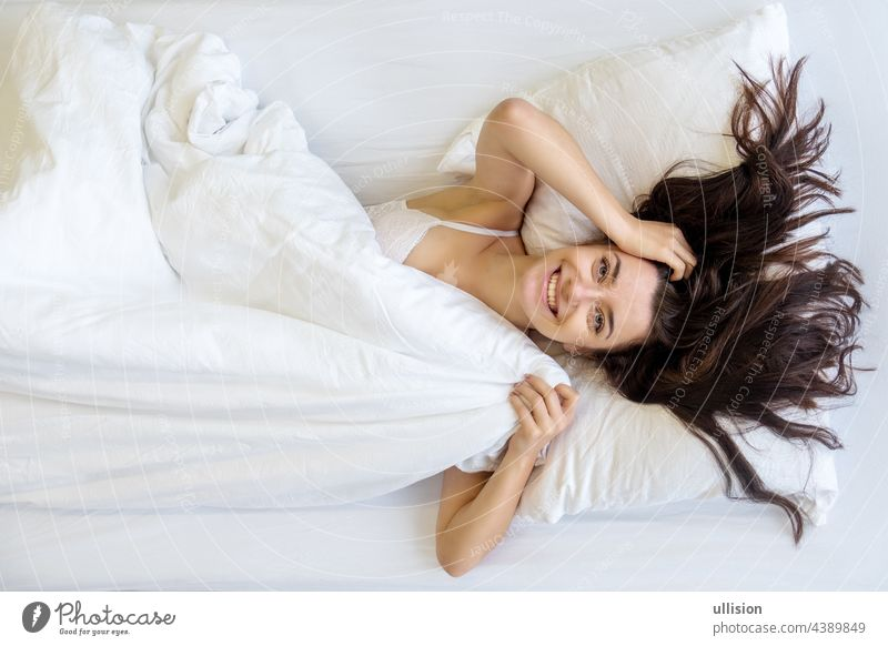 View from above to an attractive, young, sexy dark brown haired woman, smiling, laughing, enjoying the fresh soft bed, in the morning, copy space. smile