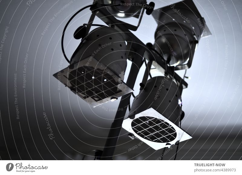 Studio lamp with four aluminium spotlights, each fitted with a protective grille and mounted on a crossbar so that they can be rotated and swivelled in all directions, photographed obliquely in monochrome