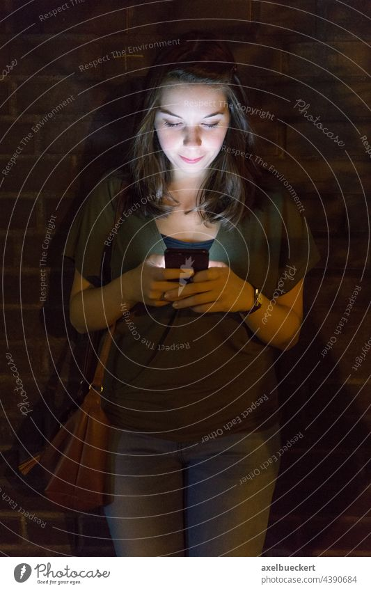 young woman uses mobile phone in the dark Cellphone using smartphone Light Flare Lighting Illuminate Technology Lifestyle Telephone Internet copywriting Screen