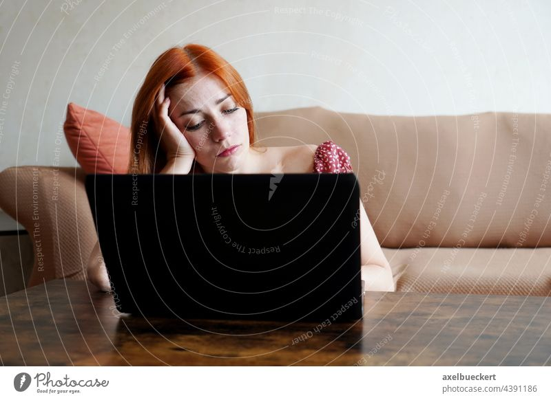 sad lonely depressed using laptop computer while working from home woman bored work from home home office real people overworked young adult frustration sadness