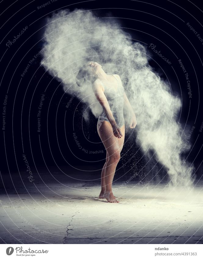 beautiful caucasian woman in a black bodysuit with a sports figure is dancing in a white cloud of flour on a black background action active adult art attractive