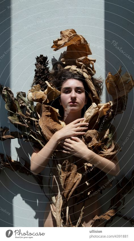 Portrait of a young sexy woman with brown hair artfully decorated covered by leaves of dry, withered banana tree, looking like an art nouveau girl, foliage