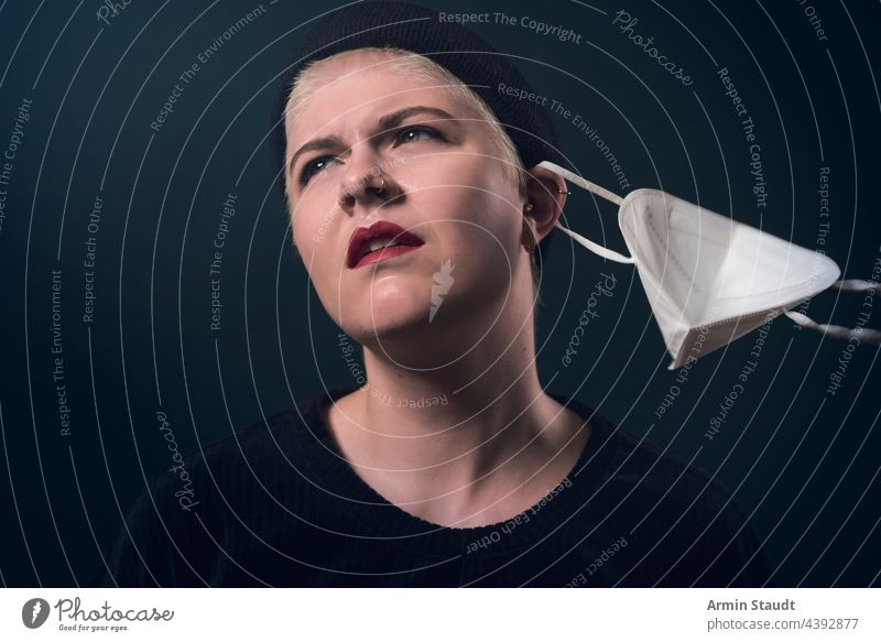 Studio portrait of a young woman who frees herself from the corona protective mask studio serious confident looking irritated refuse strong powerful piercing