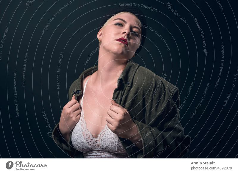 portrait of a young woman with a man's shirt, cap, and bustier studio confident heart love passion finger serious strong power powerful short hair business shy
