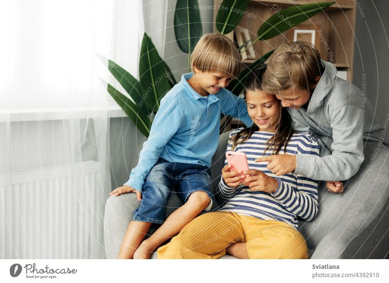 Children sit at home on the couch, play games on the phone, chat with friends. Modern technology and spending time at home tablet cute sister brother gadget boy