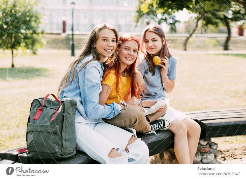 Three schoolgirls are sitting on a park bench, talking, preparing together with the lesson. The concept of training and education students laptop friendship
