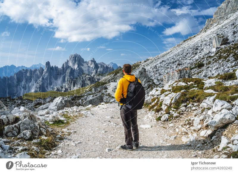 Man in yellow jacket hiking in Tre Cime National park. Cadini di Misurina in the background. Dolomites, Italy, Europe dolomites italy man cadini misurina