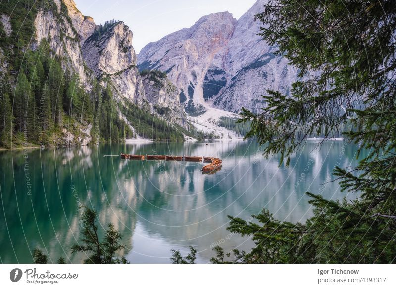 Wooden rowing boats at calm lake Braies or Pragser Wildsee during sunset pink light. Dolomites, Italy braies pragser wildsee wooden travel nature tourism italy