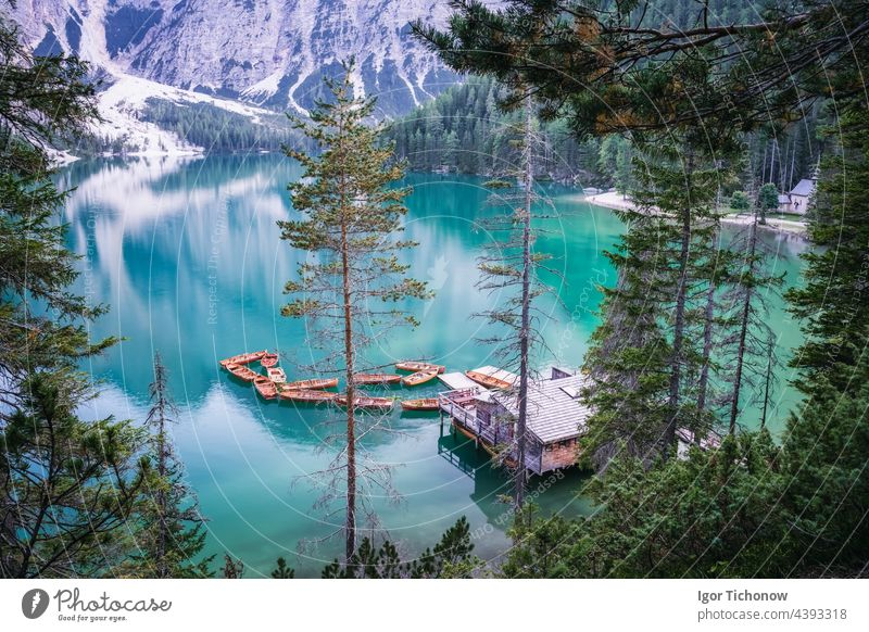 Boathouse and wooden boats at Braies or Pragser Wildsee during sunset pink light. Dolomites, Italy braies lake pragser wildsee calm travel nature tourism italy