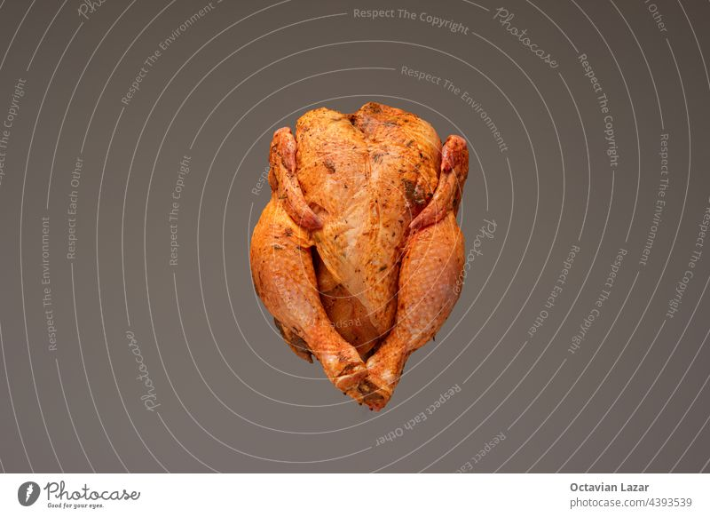 Fresh whole chicken, raw and ready seasoned. Close up studio shot, isolated on brown background studio light nobody paprika red orange close appetizing snack