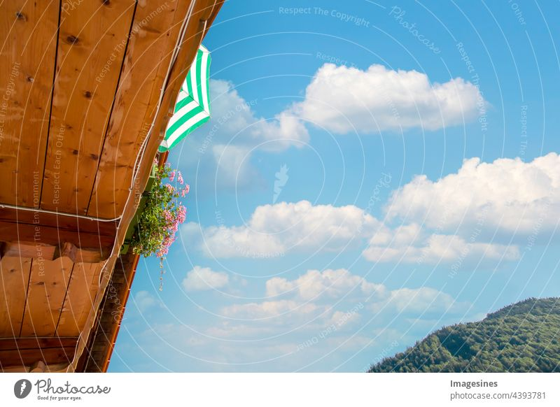 Balcony. Balcony with parasol and cloudy sky. Relaxing on a balcony in bloom in summer. Summer holidays vacation at home. relax at home. balconies Sunshade