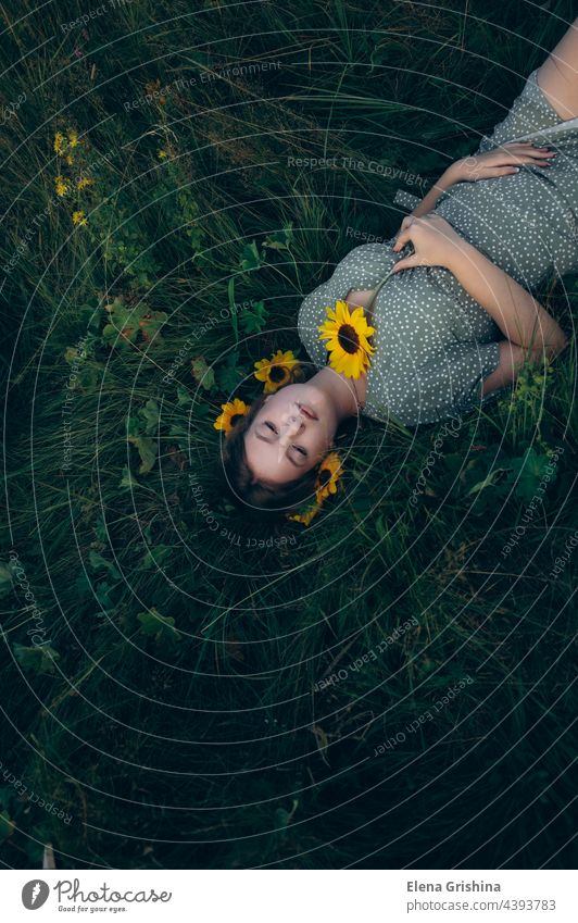 Portrait of a young girl lying on the grass among flowers. portrait sunflower dress summer beautiful femininity smile hair chain pendant youth rest slowdown