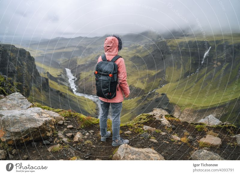 Close up of a woman with backpack enjoying icelandic highland and river fossa close to Haifoss waterfall in Iceland haifoss tourist travel landscape nature