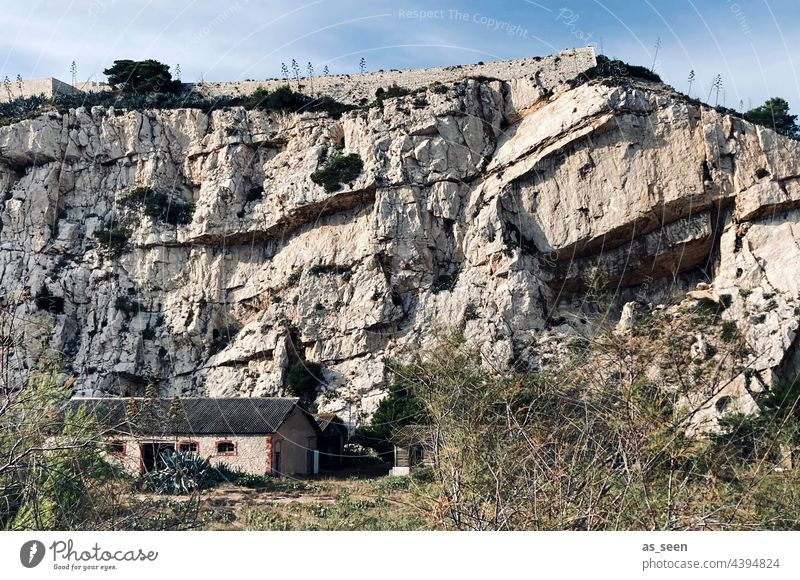 Rock face with house rock stone House (Residential Structure) Small Sky Light Dry undergrowth Massive antagonistic Gray rock strata Exterior shot Colour photo