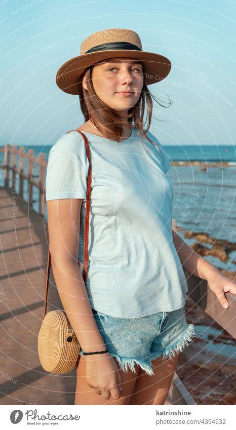 Teen girl standing on wooden bridge by the sea sunset teenager adolescent blue mockup Caucasian straw hat walkside sidewalk outdoor vacation travel wearing