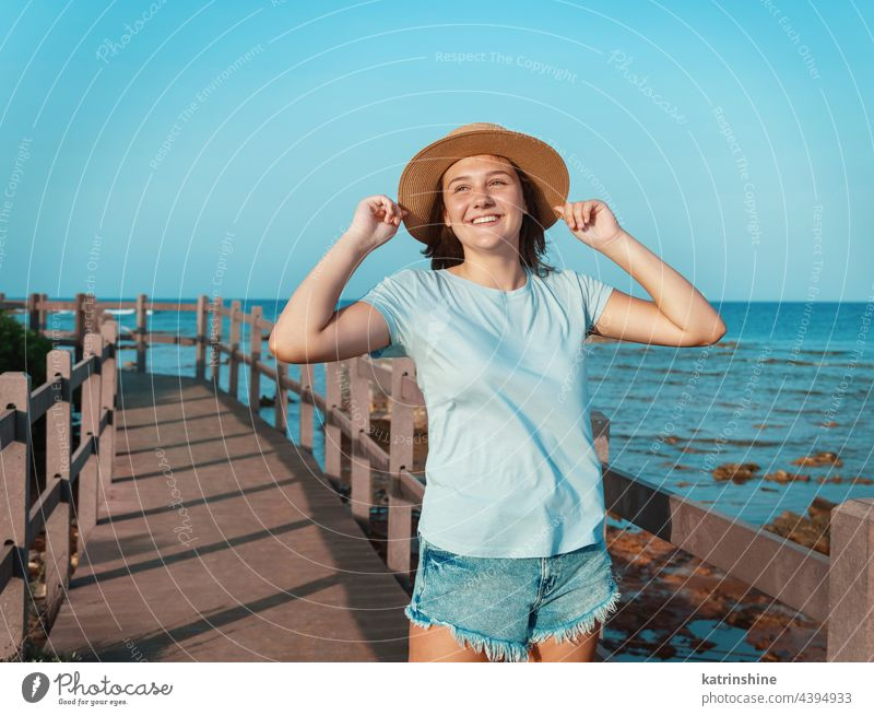 Teen girl standing on wooden bridge by the sea sunset teenager adolescent blue mockup Caucasian straw hat walkside sidewalk outdoor touch vacation travel