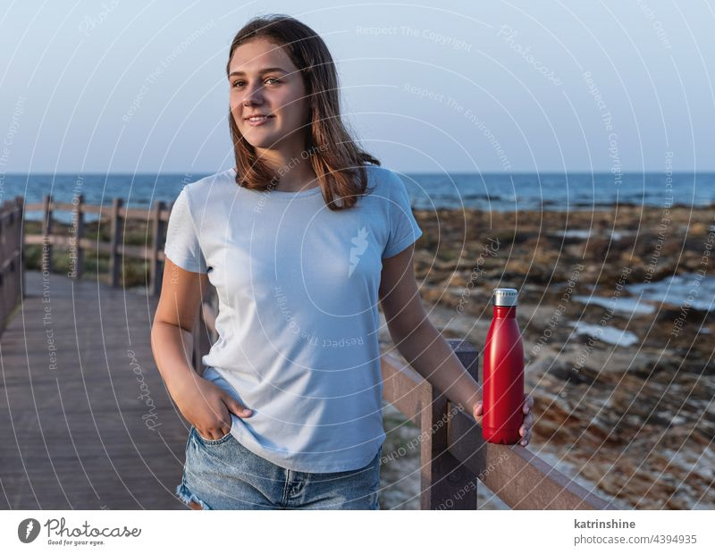 Teen girl in t-shirt standing and holding reusable water bottle in hands teen sea sunset mockup red blue light blue close up metal template jeans copy space
