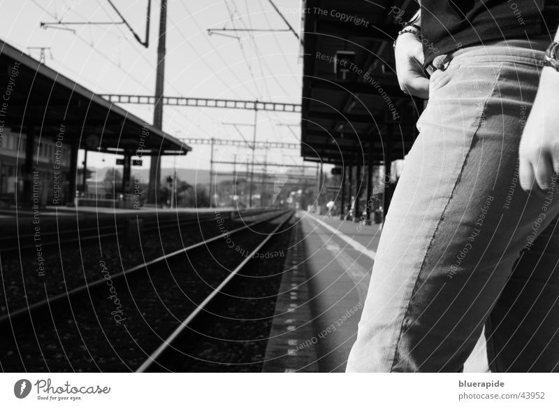Just before Clock Cable Human being Woman Adults Hand Legs Train station Railroad Pants Line Stand Wait Black White Time Railroad tracks Risk Resolve Platform