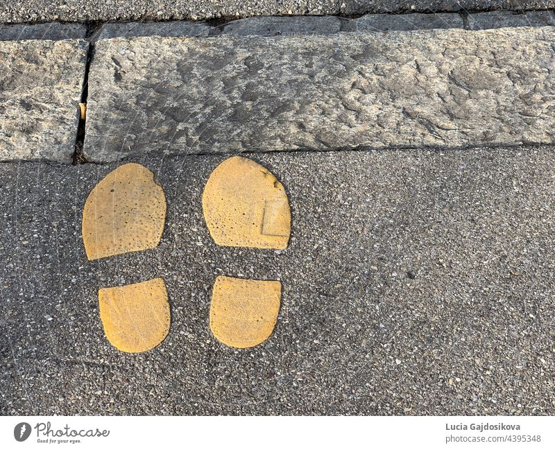 Two shoe imprints painted in yellow color on the edge of a sidewalk. Symbol for road crossing. There is copy space available. painted shoe imprints symbol