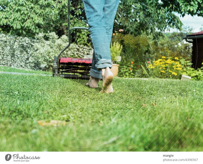 A woman barefoot mowing the lawn in the garden Lawn Mow the lawn Meadow Garden Gardening Feet Barefoot Lawnmower Grass mares Exterior shot Colour photo