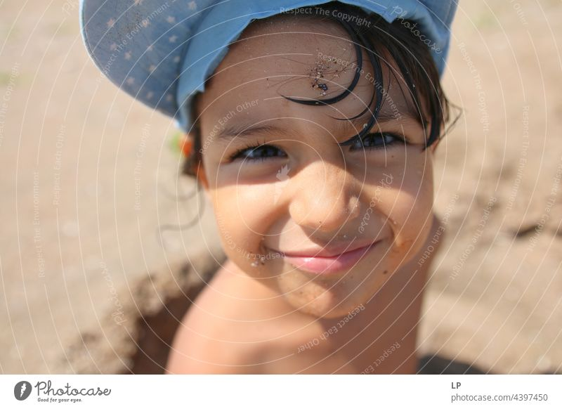 face of a beautiful child smiling at the camera on the seashore positive emotion smile Ocean Beach Individual Isolated Single Abstract Movement Flow