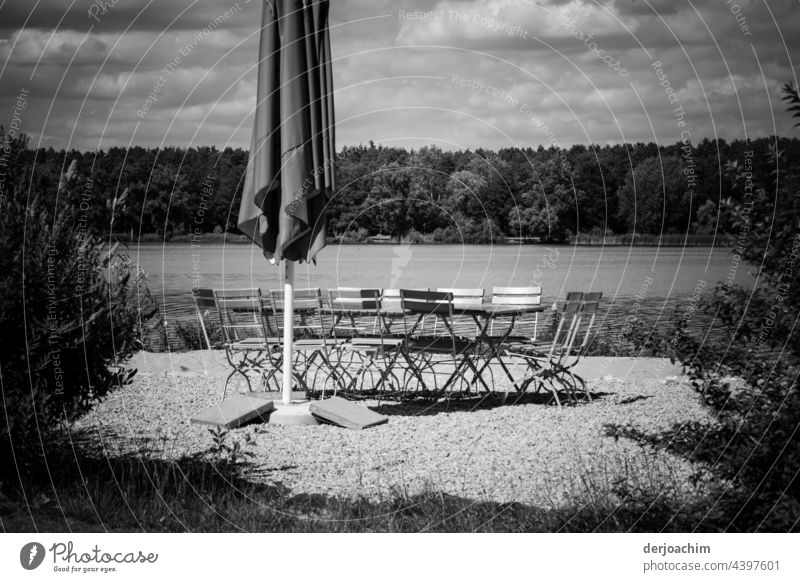 A folded parasol, a few empty chairs and table, and the water from a lake and in the background a lot of forest. To everything in the sky many clouds. Now only the guests are missing...