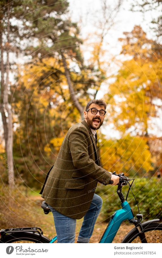 Young man with electric bicycle in the autumn park young nature lifestyle outdoor activity color ride summer bike day leisure people ebike travel sport city