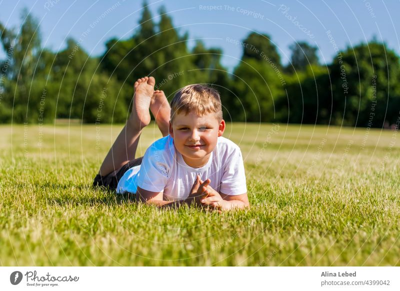 A cheerful child smiles with joy. I am happy to walk and play on the lawn in warm sunny weather in the park. the emotions of children on the face. boy happiness