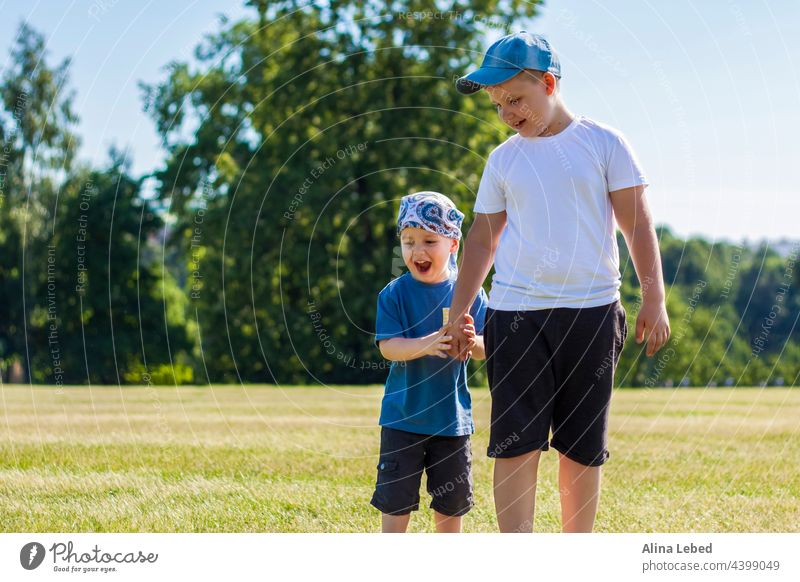 Cheerful children, two brothers, smile with joy. we are happy to walk and play on the lawn in warm sunny weather in the park. the emotions of children on the face.