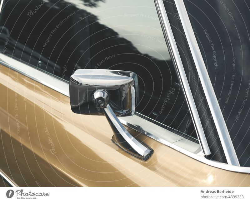 Sideview mirror of an old vintage car, close-up antique glass side golden yellow beige chrome reflection sideview window front detail shiny round classic