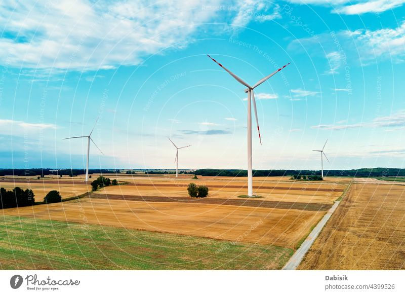 Windmill among agricultural fields. Wind turbine generator at summer day. Wind energy concept, Suistanable and renewable energy for climate protection windmill