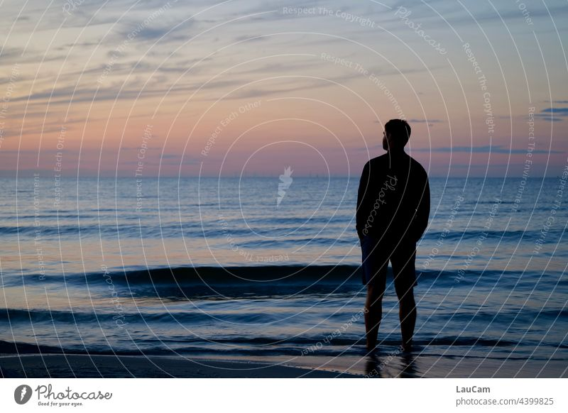 The sun has just set. In the evening atmosphere, a man stands on the beach in the water and looks into the distance.... Sunset Beach Twilight Twilight sky Ocean