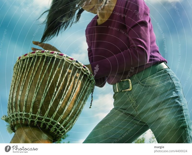 A woman drums djembe Woman Drum Drum set Music Rhythm Drummer tool Beat Concert good-looking Sound Practice Musician Live Sky Clouds Blue Blue sky Jeans