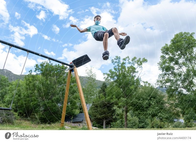 young guy wearing a sanitary mask makes a huge jump from a swing on a playground, leaping into the empty jumping flying face mask childhood outdoors boy fun