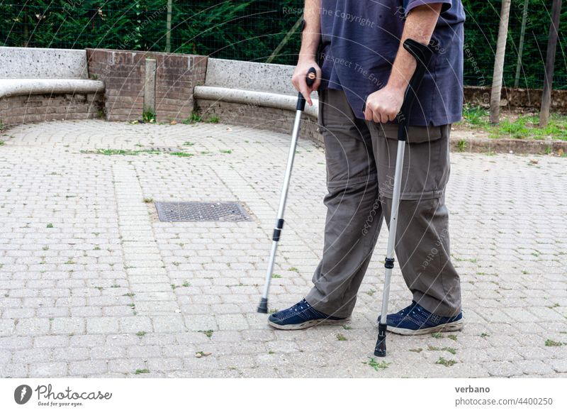 man walking with the aid of a pair of clutches pain senior health elderly copy space lifestyle people outdoor portrait summer disease illness insurance park