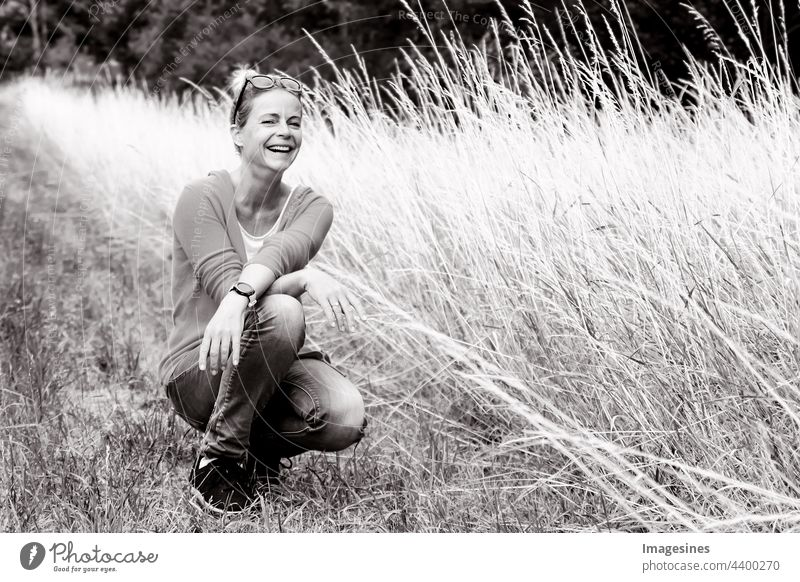 Black and white portrait of smiling happy and charming woman looking at camera. Portrait of woman in summer squatting on a meadow. black-white smilingly