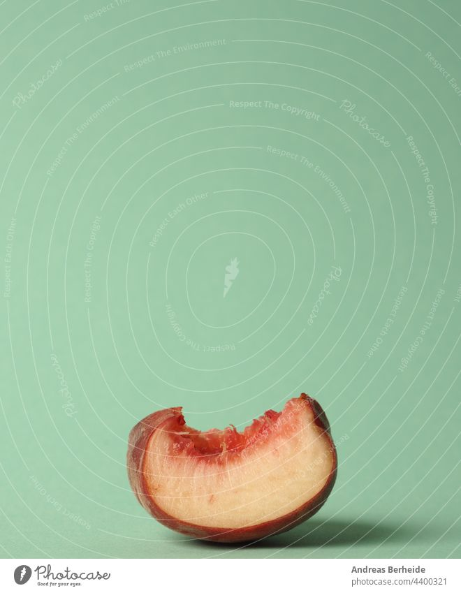 A piece of a flat peach on a green background part freshness nobody diet detail nutrition pastel vitamin sweet juicy organic ripe vegetarian summer colorful