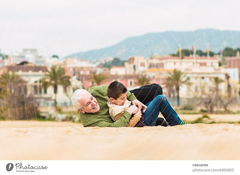 Funny boy and his grandfather playing stretched out in the sand on the beach active caucasian child childhood cute el masnou family fun generation generations
