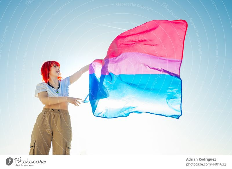 Woman holding the Bisexual Rainbow Flag with the blue sky in the background flag lgbt homosexual bisexual pride lesbian rights lgbtq rainbow love homosexuality
