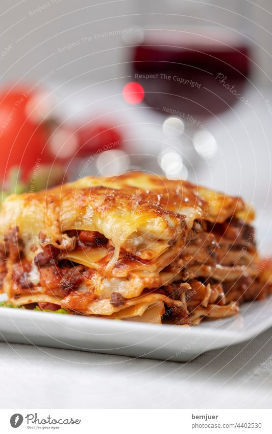 Portion of lasagne on a plate Lasagne Plate Tomato Red Vine Glass Lettuce Eating sauce Basil pasta Italian Meat Beef Bolognese Cheese Fresh baked Lunch