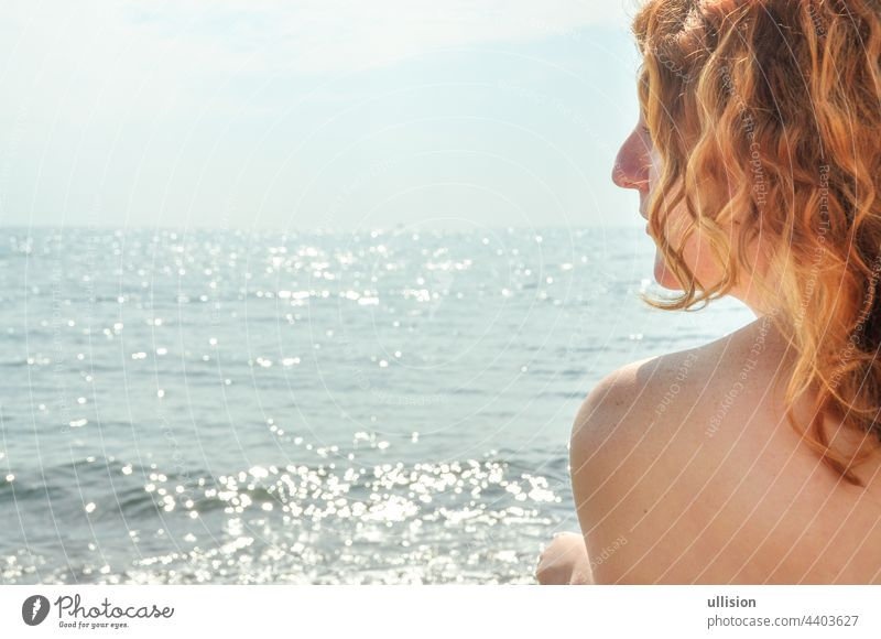Beautiful portrait in profile closeup of a young red-haired curly woman by the sea on the beach in Italy with copy space, space for text red hair italy girl