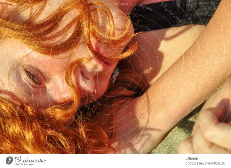 Beautiful portrait in closeup of a young elegant sexy red-haired curly woman on the beach full of love and desire Love Redhead Woman Lying Holiday Sea Italy