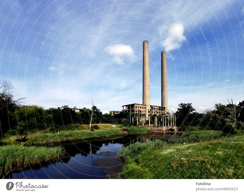 Lost Place - an old power plant on the Oder River that was built but never put into operation. 2 chimneys rise into the blue, slightly cloudy sky. lost place